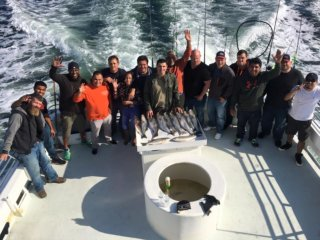 group on back of boat fishing